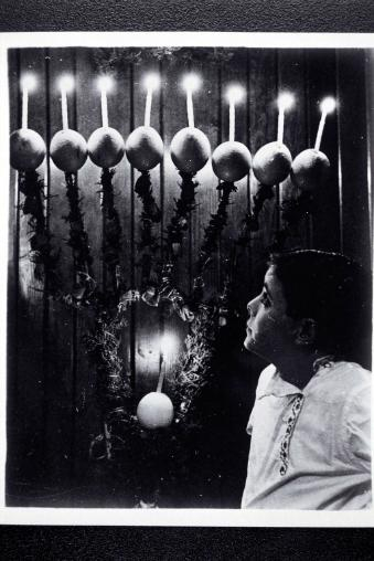 A child in front of a Hanukkah lamp made of oranges.